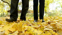 man and woman walking on the fallen leaves in autumn park, slow motion 3 - stock footage