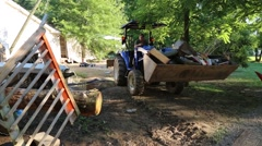 Man Driving Tractor and Carrying Debris from Flood Damaged Home - stock footage