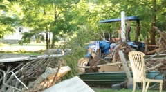 Man Driving Tractor in Background of Debris from Home Wrecked by Flood Stock Footage