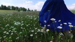 Girl runs on a green field with daisies slow motion Stock Footage