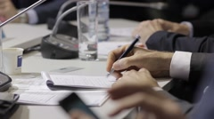Man's hand writes notes in a very important point. International Forum, a busine Stock Footage