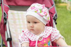 little newborn girl sitting in a baby carriage - stock photo