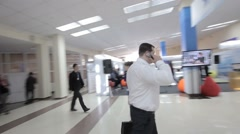 Businessman in white shirt goes down the hall at the international forum. The ca Stock Footage