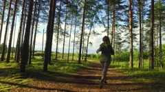 Young Female running among trees in  forest. Slow motion footage. Amazing sun Stock Footage