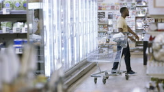 4K Happy carefree young man dancing as he does his shopping in supermarket Stock Footage