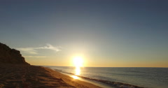 Sea surf at sunrise on a wild beach with a sandy slope in summer Stock Footage