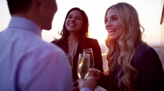 Group of multi ethnic managers toasting with champagne on rooftop at sunset Stock Footage