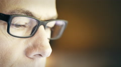Closeup of a man wearing glasses looking at a computer screen 4k Stock Footage