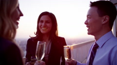 Happy multi ethnic business colleagues toasting success on sunset rooftop Stock Footage
