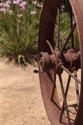 rusty western wagon wheel background - stock photo