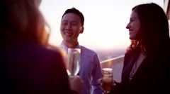 Multi ethnic business people celebrating success on city rooftop at sunset Stock Footage