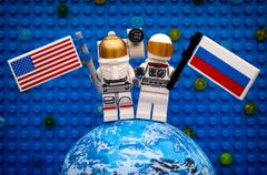 Two Lego spaceman minifigures with American and Russian flags stay on planet - stock photo