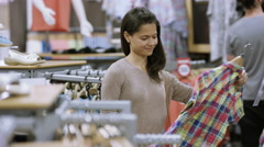 4K Customer shopping in clothing store goes to register to make a purchase Stock Footage