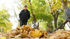 adult man kicking a bunch of yellow fallen leaves in autumn park, slow motion 3 - stock footage