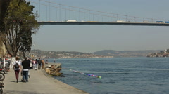 Vehicles pass the Bosporus bridge and local people and tourists  walk Stock Footage