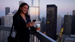 Hispanic businesswoman using smartphone technology drinking coffee on rooftop Stock Footage