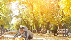 little boy throwing fallen leaves in autumn park, slow motion 1 - stock footage