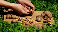 Hands of young woman cracking nut with hammer on wooden surface Stock Footage