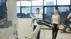 4K Woman with personal trainer using treadmill in modern gym Stock Footage