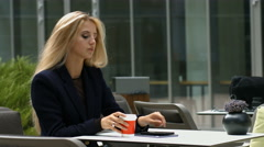 Attractive business blonde woman using smartphone and coffee Stock Footage