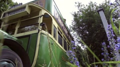 Tourists on open top vintage bus drive through a British country lane Stock Footage