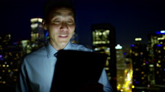 Portrait of ethnic businessman video call with his client on rooftop at night Stock Footage