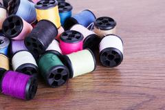 Scattered cotton reels on a wooden surface Stock Photos