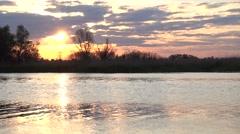 Declining sun between clouds above river Stock Footage