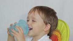 Baby boy drinks water from a bottle Stock Footage