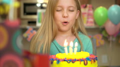 A young girl blows out birthday candles at her birthday party.  Stock Footage