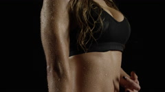 Woman traces definition line down her abs. Dolly in. Slow motion. Over black. Stock Footage