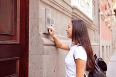 Pretty visiting girl with a back pack buzzing the intercom at a wooden door w Stock Photos
