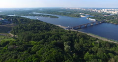 Subway Bridge across the Dnieper River in the city with lots of green trees on a Stock Footage