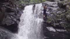 Guy jumping from waterfall in natural pool Stock Footage