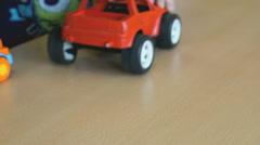 Children play toy model cars at the table Stock Footage