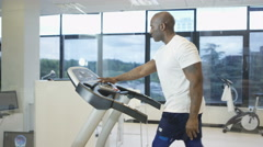 4K Man using treadmill in gym with view of natural environment on video screen Stock Footage