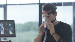 4K Sports professional analyzing man's fitness levels with hi tech equipment Stock Footage