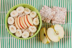 Oatmeal Porridge with Apple and Bananas Slices in Green Bowl Stock Photos