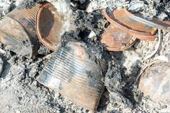 Discarded burnt tin cars lying in a pile of ash from a burnt fire outside. Stock Photos