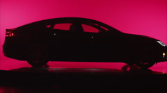 Wide angle silhouette of electric car, static against red background Stock Footage