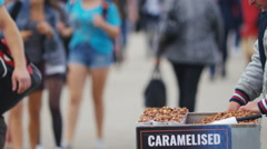 4K Anonymous street vendor making caramelised nuts, in slow motion Stock Footage