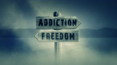 Old Wooden Sign on a Middle of a Cross Road With the Words Addiction or Freedom Stock Footage