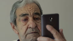 Closeup of an Old Man Reads SMS on a Mobile Phone - stock footage