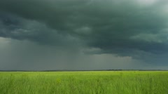 timelapse with dark storm clouds over field - stock footage