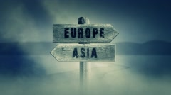 Old Wooden Sign on a Middle of a Cross Road With the Words Europe or Asia Stock Footage
