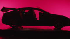 Wide angle silhouette of a car against red background, trunk closes Stock Footage