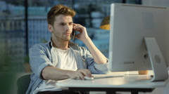 4K Young man using computer & talking on cell phone in city apartment - stock footage