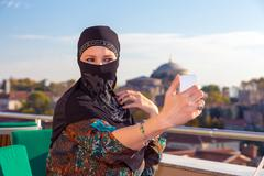 Lady in Black Hijab Holding Telephone - stock photo