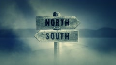 Old Wooden Sign on a Middle of a Cross Road With the Words North or South Stock Footage