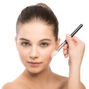 Young brunette woman with clean face. Girl perfect skin applying cosmetic brush - stock photo